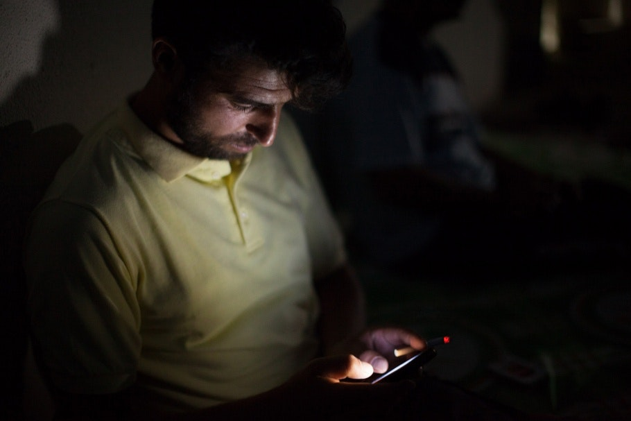 A man in yellow shirt looking at his cell phone.