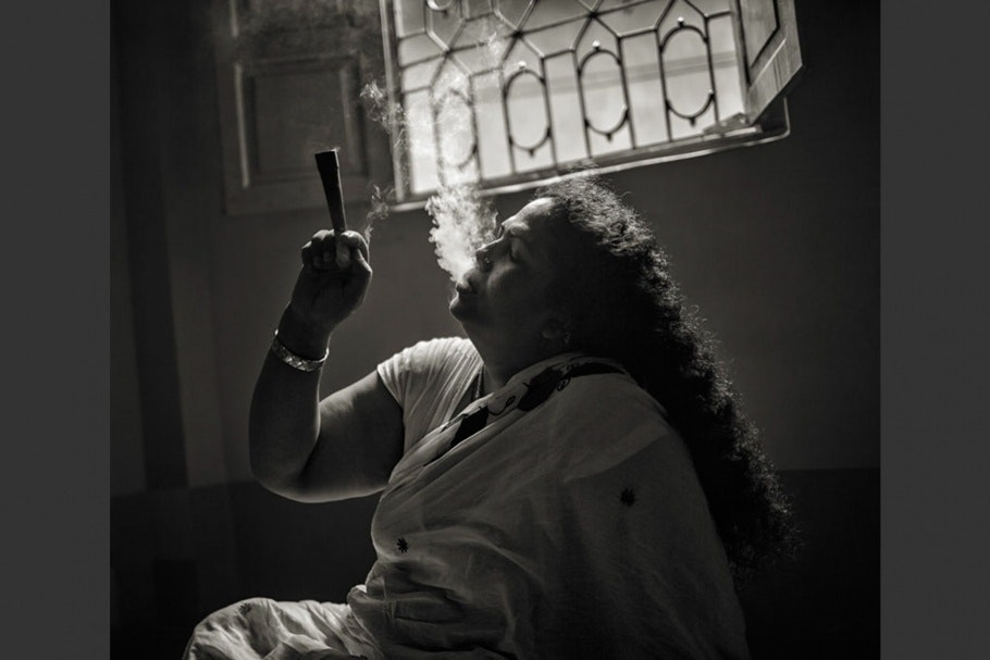 A Bangladeshi hijra woman smokes a pipe