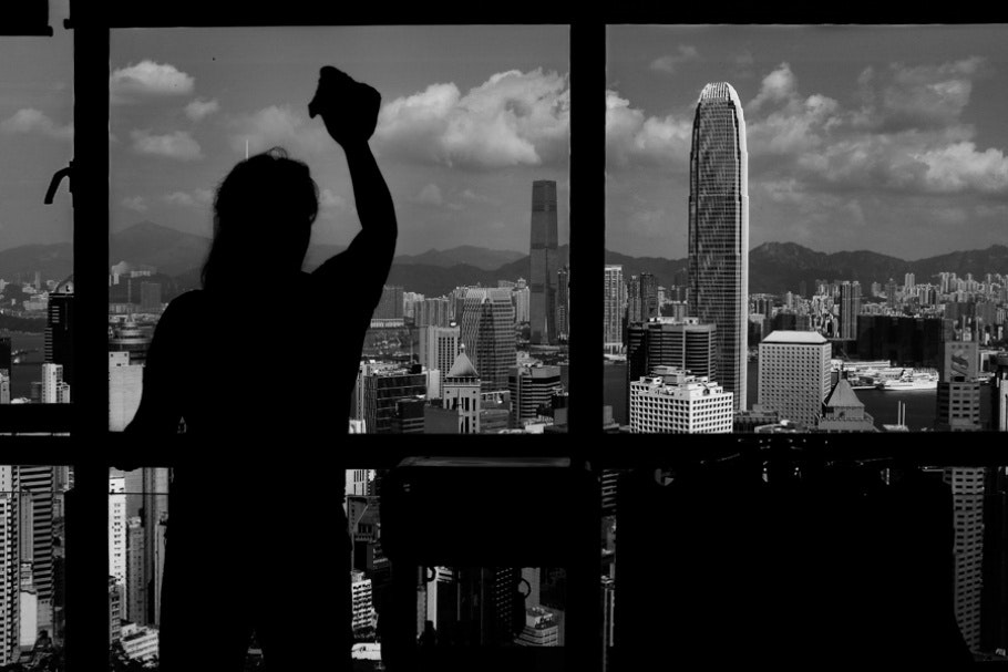 A woman cleaning the window of a skyscraper.