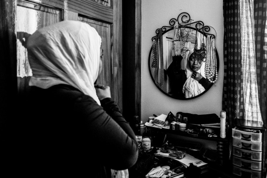 A woman wearing a headscarf and looking in a mirror.