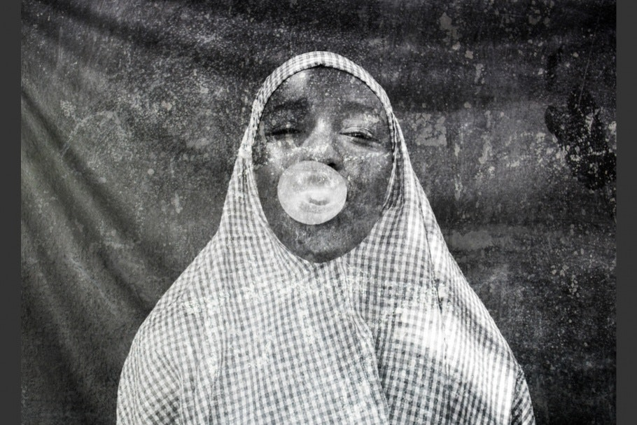 A woman blowing a gum bubble.