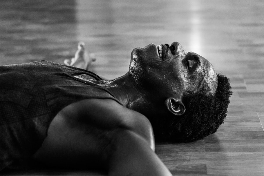 A man in a tanktop, sweating and lying on the floor.