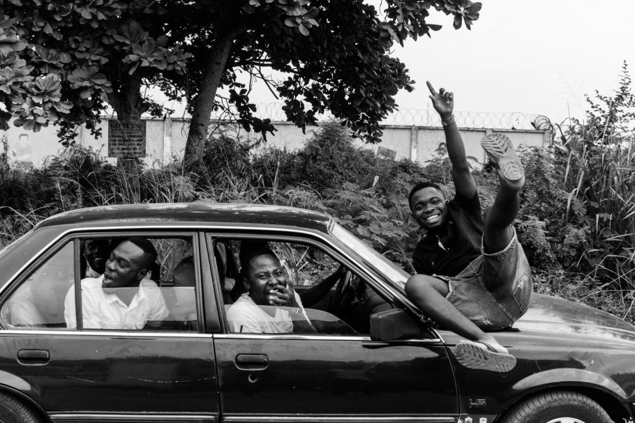 A group of men in a car laughing while one sits on the hood.