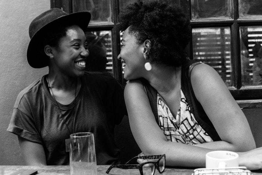 Two women sitting at a table, laughing.