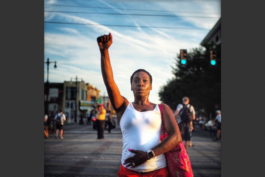 A woman standing in the street with her fist raised.