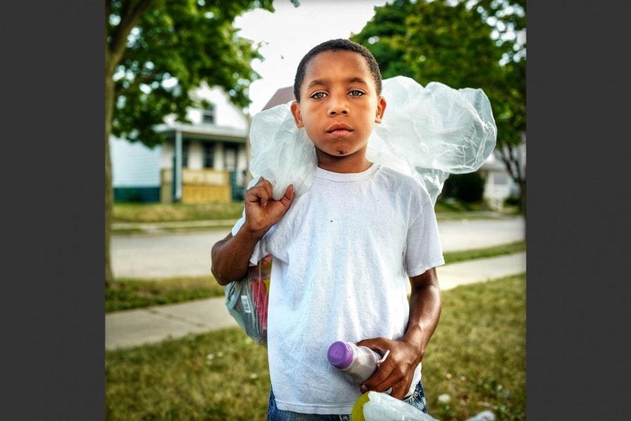 A boy holding a plastic bag over his shoulder.