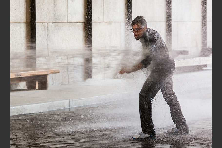 Dread Scott standing while being sprayed by high-pressure water jets.