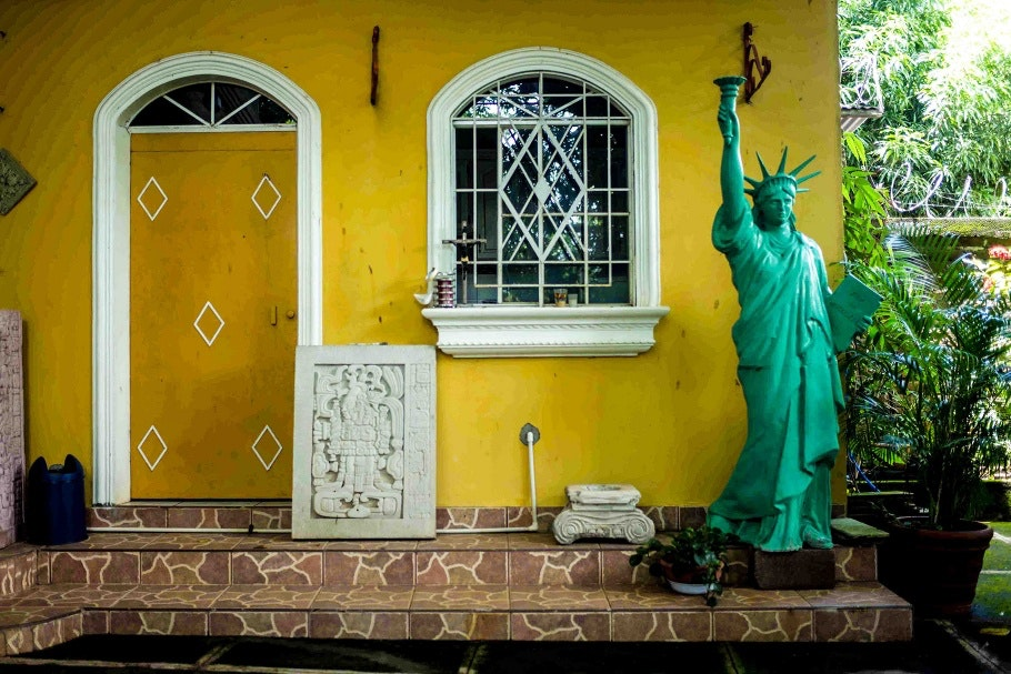 A small replica of the Statue of Liberty in front of a house