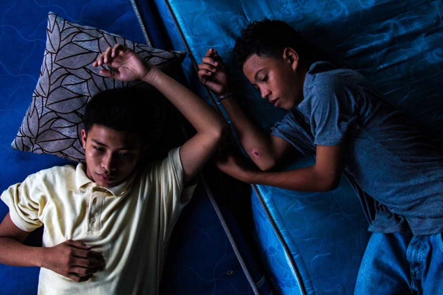 Two boys lying on mattresses