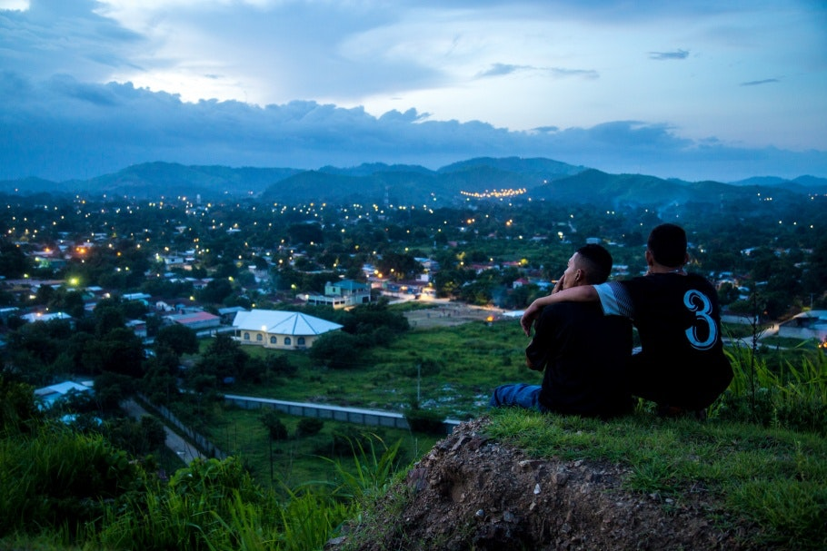 Two men sit on a hillside, smoking