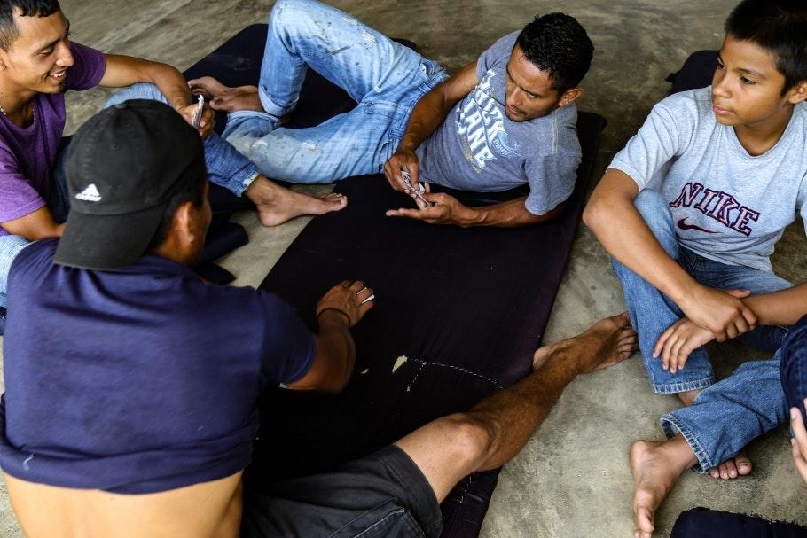 Men sitting on mats, playing cards