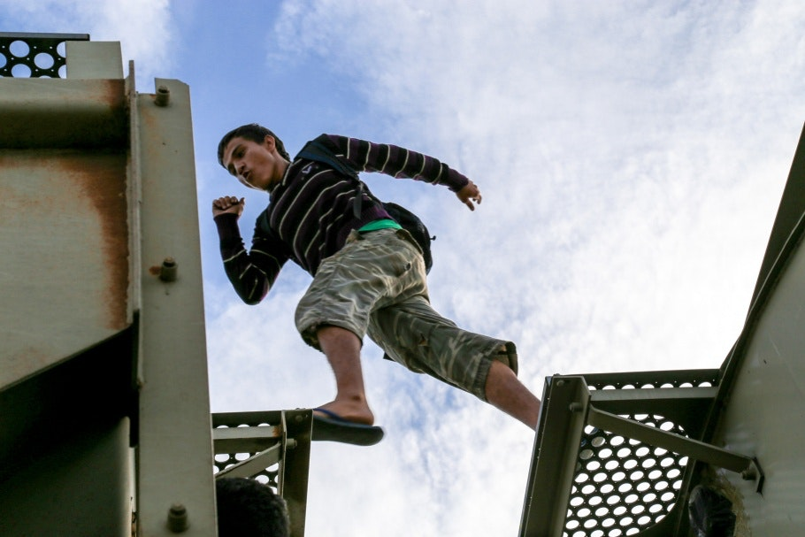 A young man jumps between train cars