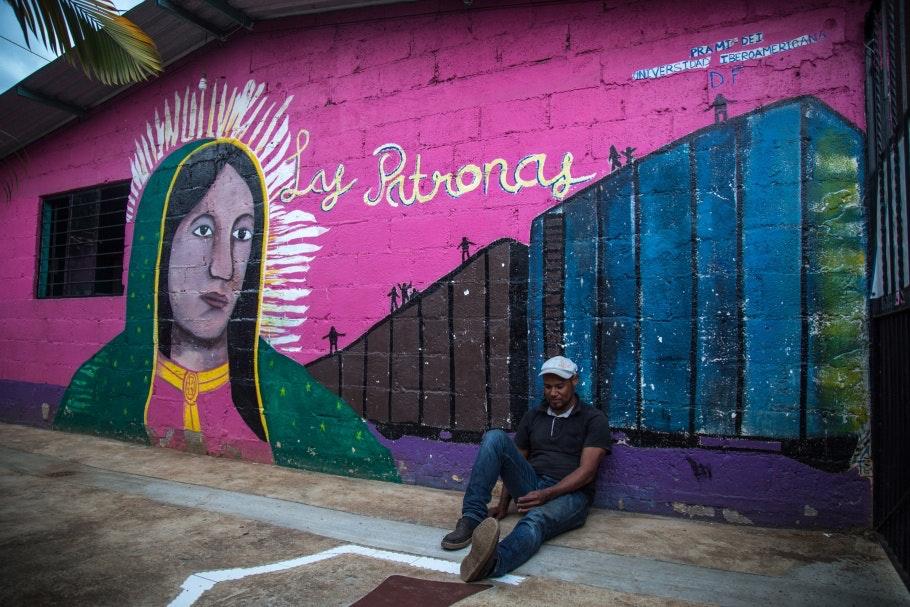 A man sitting down against a mural
