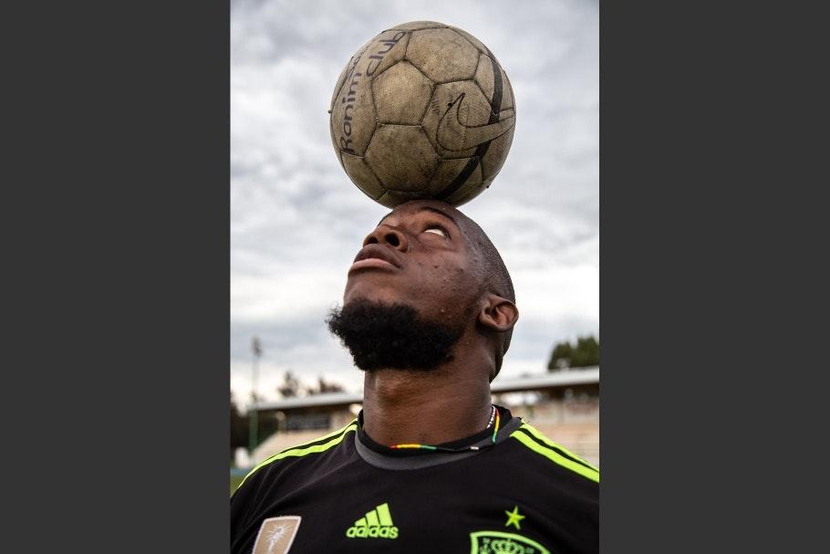A man balancing a soccer ball on his head
