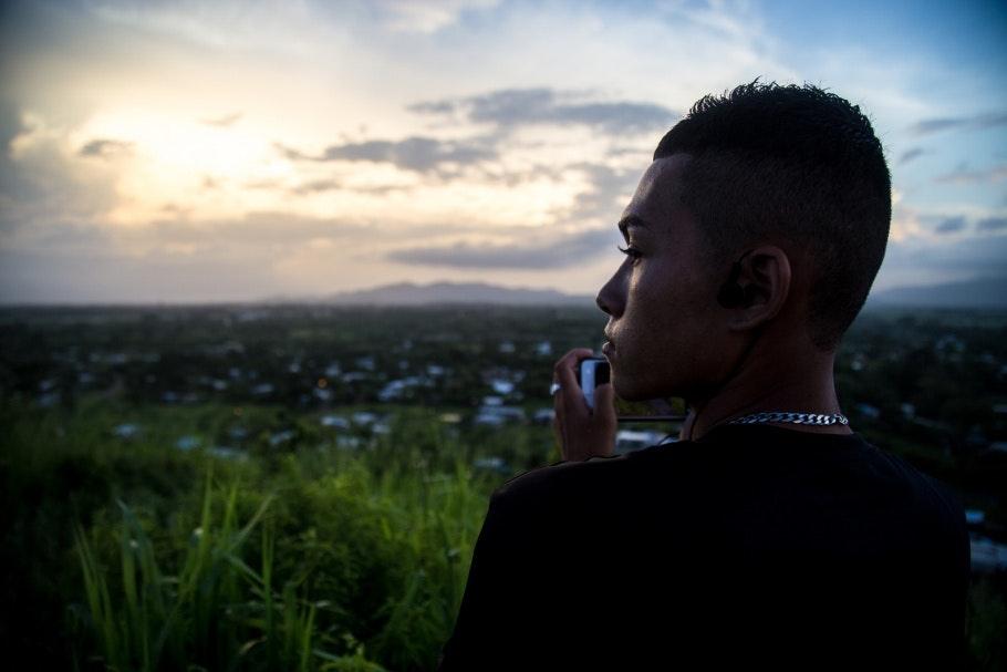 A boy stands on a hillside overlooking homes below