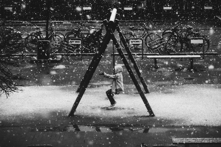 Snow falls while a girl sits on a swing