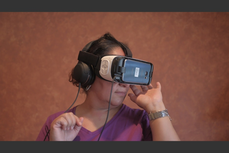 A woman wearing virtual reality goggles and headphones