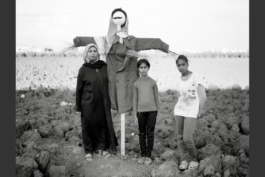 A woman and two girls stand next to a scarecrow