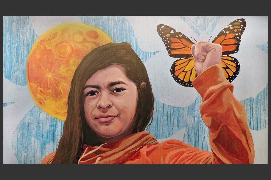 A mural of a woman with a fist up and a butterfly in the background