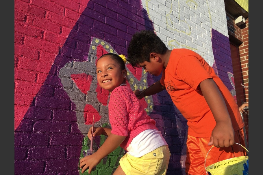 A girl and a boy painting a mural
