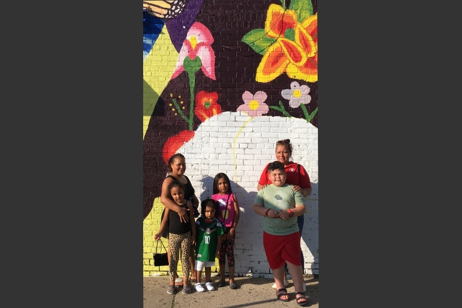 Two women and children posing in front of a mural