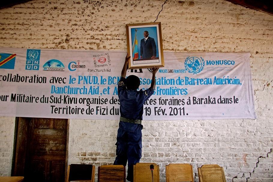 Man hanging a photo of Joseph Kabila.