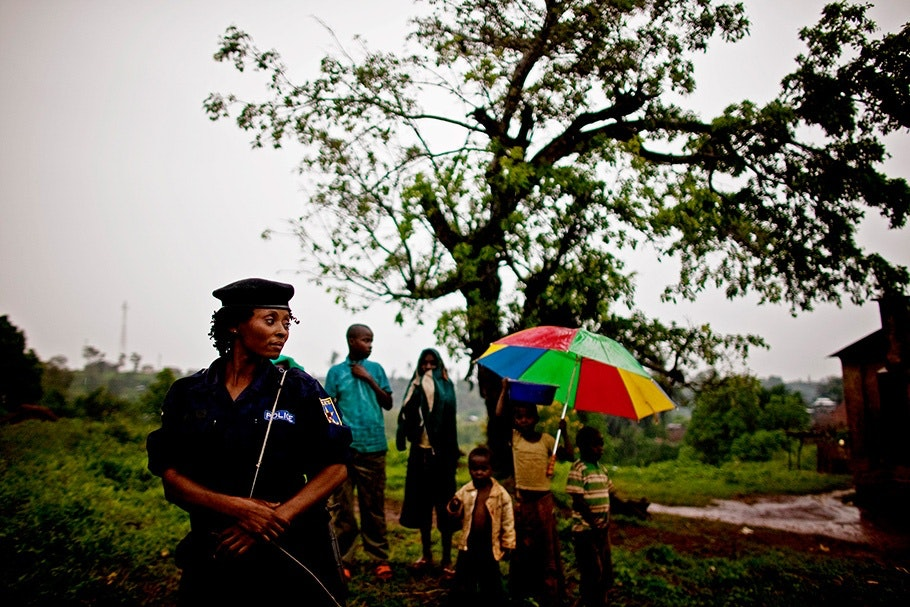 A policewoman standing guard while small group looks on.