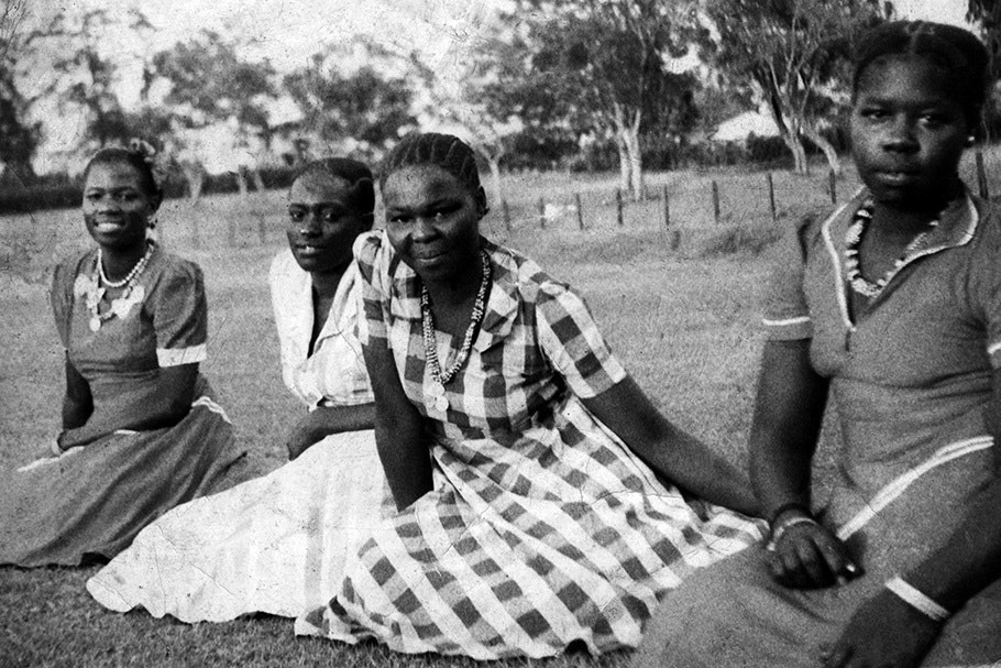 Women sitting on grass.