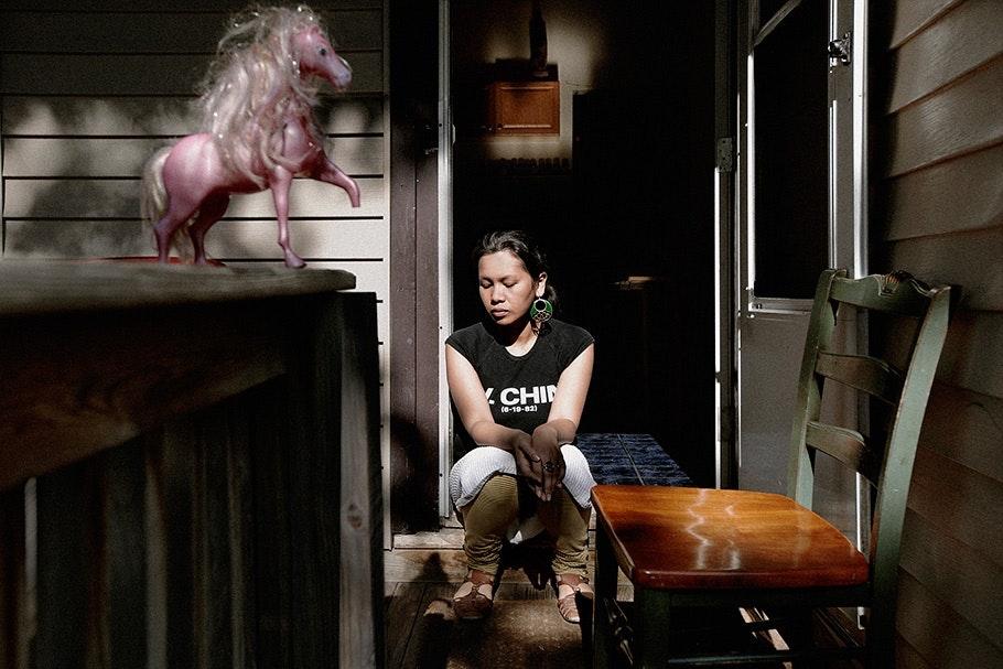 Girl sitting near a toy horse.