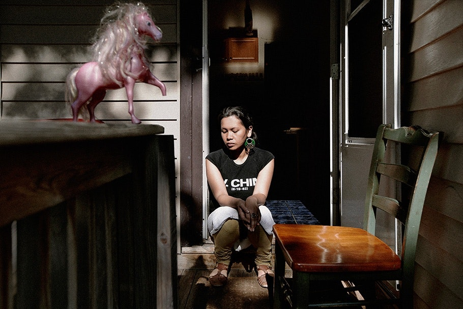 Girl sitting near a toy horse.