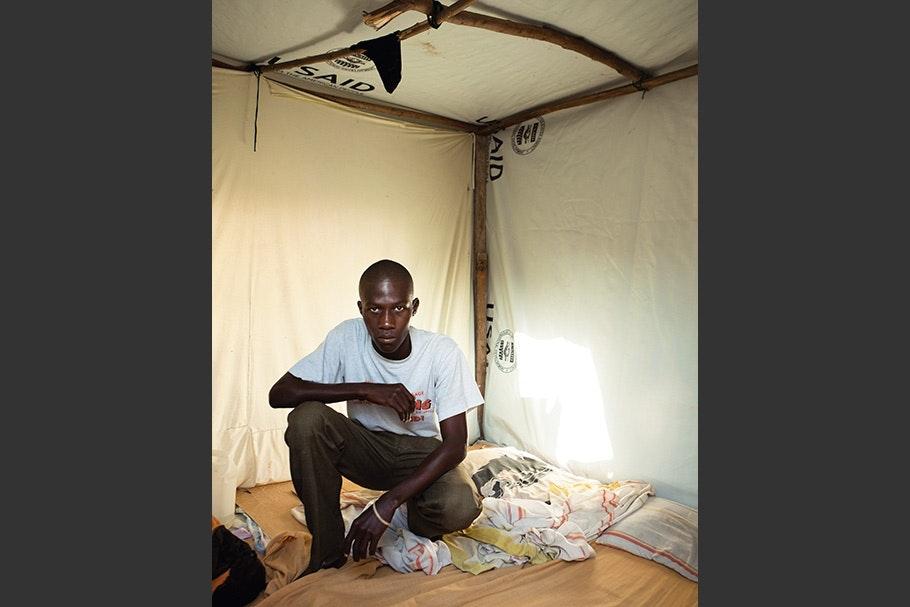 Man kneeling inside a tent.