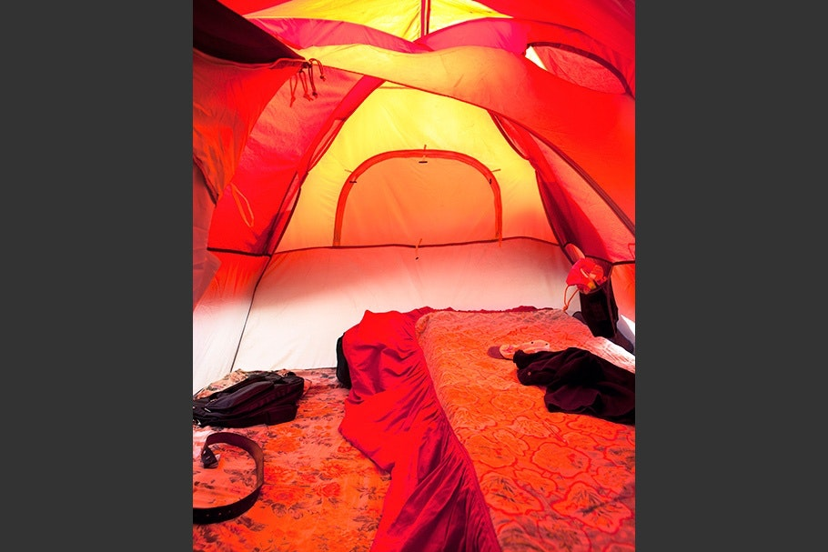 A bed in an orange tent.