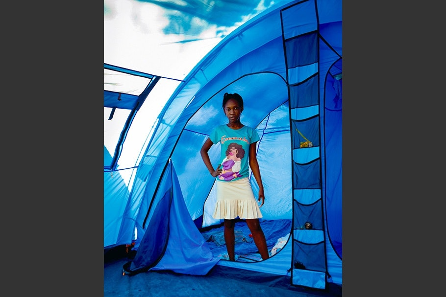 Girl standing at entrance to a tent.