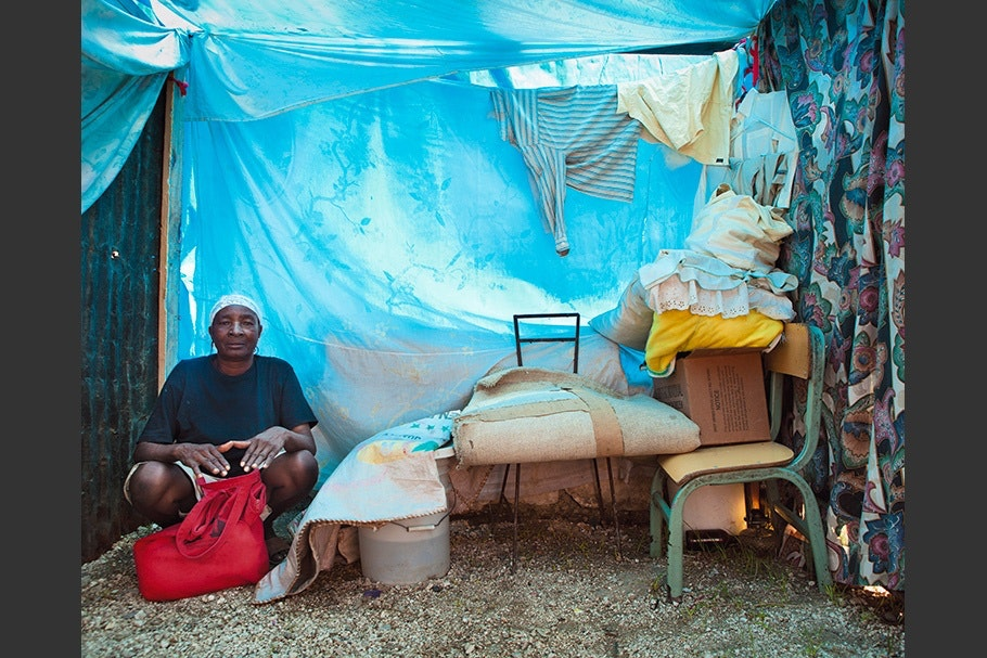 Woman sitting in tarp-covered home with possessions.