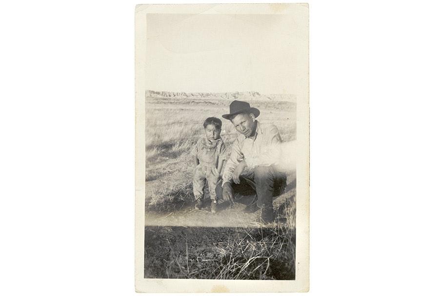 Moses Bull Man kneeling next to a boy.