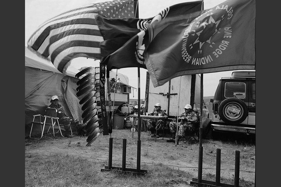 Men sitting near flags.