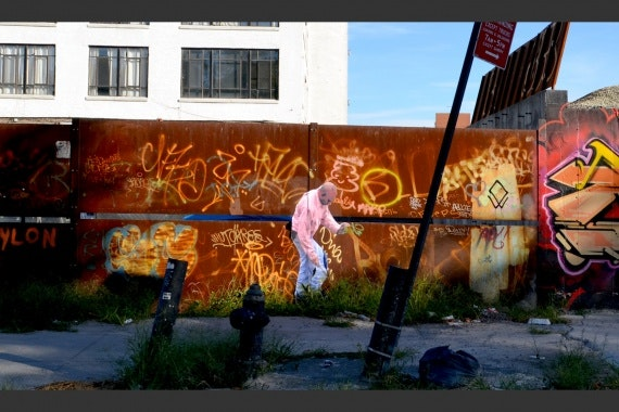 Cut-out figure of man pasted onto rusted and graffiti-covered wall
