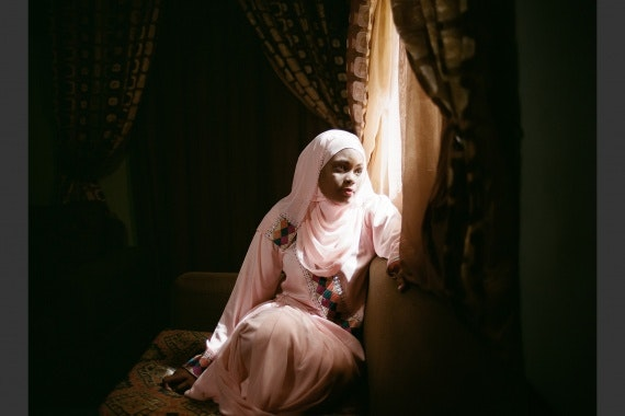 A Nigerian romance novelist sits at her window