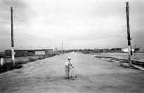A man with a walker in the middle of a rural road after a tornado.