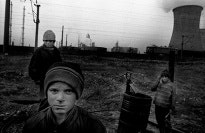 Three boys in front of a power plant.