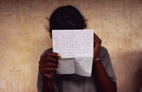A girl holds a letter in front of her face.