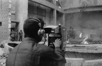 Panorama of a film set with a cameraman in the foreground.