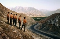 A row of men standing in the mountains.