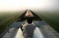 A boy riding on top of a train.