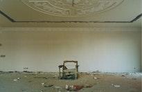 Ruined chair beneath an ornate ceiling.
