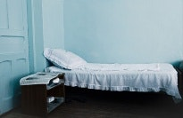 Empty bed with blue wall.