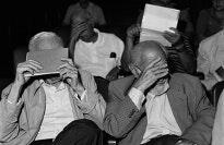Seated men hiding their faces
