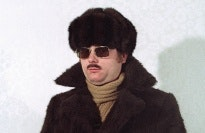 Man with fur coat and hat, wearing sunglasses