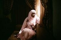 A Nigerian romance novelist sits at her window