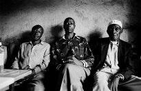 Three men sitting in a row.